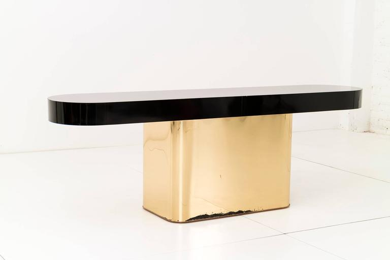 Milo Baughman console with brass plated pedestal base and black laminate top.