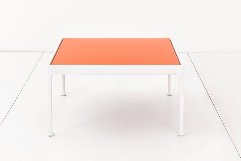Richard Schultz outdoor coffee table for Knoll. This table has a white powder-coated, cast and extruded aluminum frame with an orange enameled porcelain on steel tabletop. The table has a weather resistant finish and a slight gap between the top and