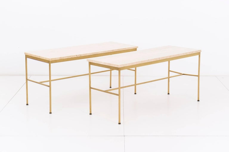 Paul McCobb for Directional. Pair of model 8704 console tables. Square tubular brass frames with travertine top. Patina on brass consistent with age and use. Stool sold separately.