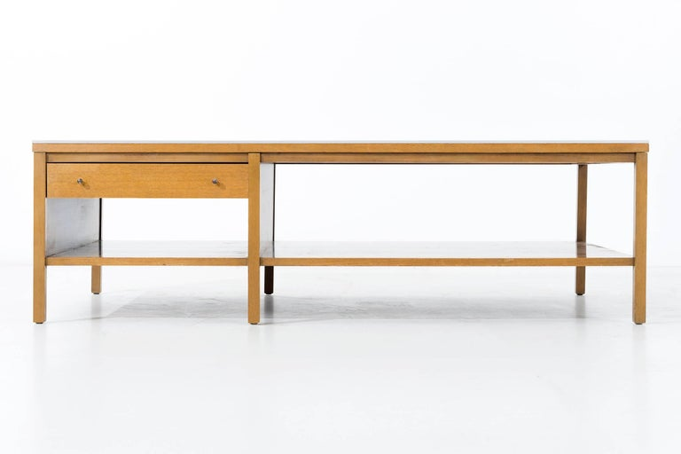 For Calvin: mahogany two-tiered table, lacquered and stained, lined with solid aluminum inlay edge. The lower tier in two sections with a single drawer on each side, with tear drop pulls.