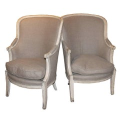 Pair of French 19th Century Barrel Back Upholstered Wing Chairs with Saber Legs