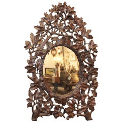 French Black Forest 19th Century Oak Leaves Carved Mirror with Oval Glass