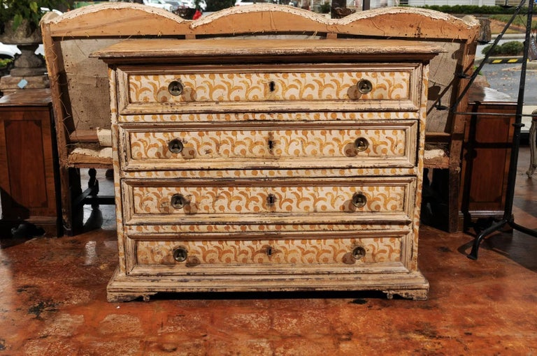 An Italian 17th century Florentine tall wooden four-drawer commode with painted floral motifs. This Italian commode was born in Tuscany, during the later years of the 17th century. Featuring a rectangular top with molded edges, the chest comprises