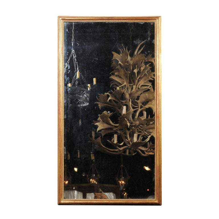 A tall French giltwood rectangular mirror from the 19th century, with beaded motifs and original mercury glass. This French giltwood mirror features an elegant linear silhouette, simply adorned with a molded frame, accented on the inside with