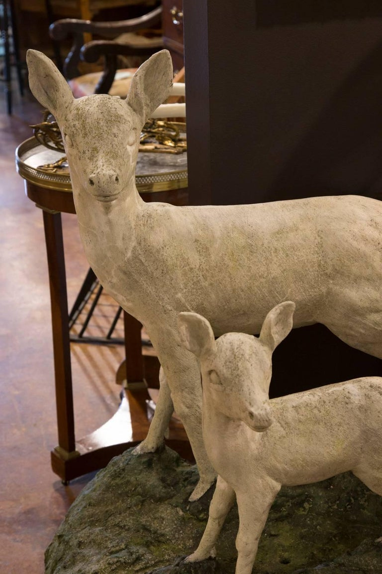 This pair of English cast stone deer sculptures was created in the mid-20th century. Featuring an alert doe with her fawn, both sculptures are placed on a single base depicting the grass on which they are walking. Both animals have raised their