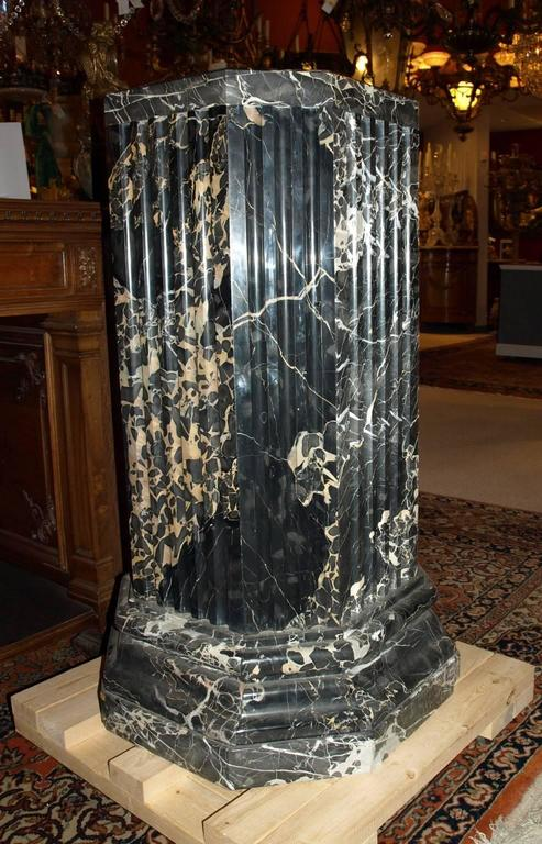 Very fine pair of portoro marble pedestals having an octagonal shape with reeded center pillar. The top is 18 inches by 18 inches. The base is 24 inches by 24 inches.