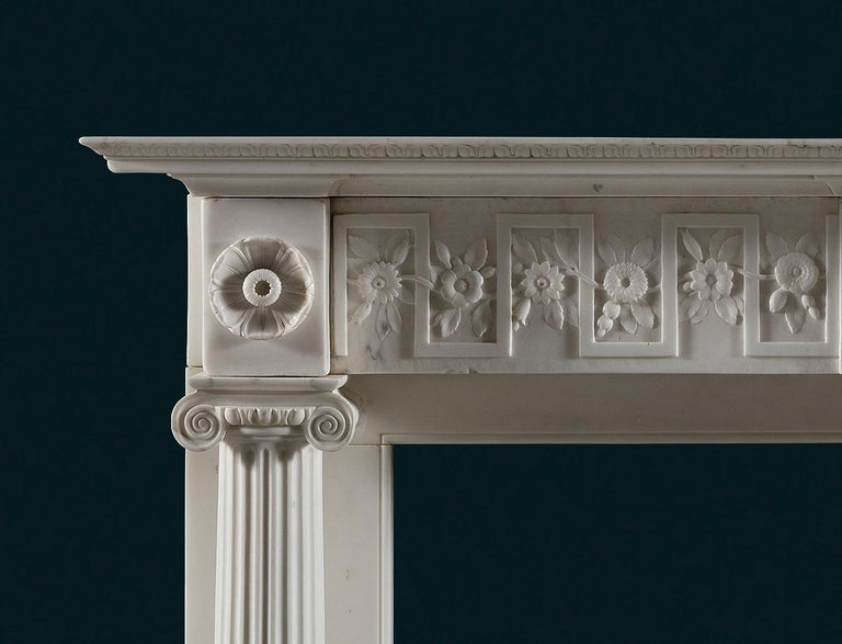 A good quality Regency period, statuary marble column fireplace made in Italy for the English market to a British Neo-Classical design.    The rectangular moulded tiered shelf above the frieze, which is centred with a rectangular plaque with a
