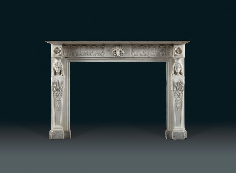 An English Regency period, neoclassical statuary marble fireplace. Carved in Italy. The herm jambs with well carved busts of the Vestal Virgins, the attendants of the temple of Vesta, the Roman goddess of fire in the Roman forum. It was their duty
