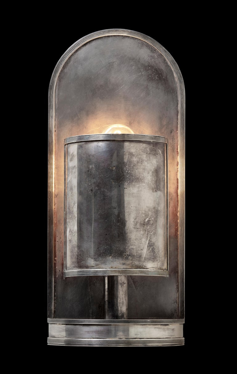 This simple and understated wall light of semi-cylindrical form is with reeded edges. The bulb is concealed behind the diffuser, creating in a soft ambient glow from the reflective back plate. An elegant solution for subtle lighting in any