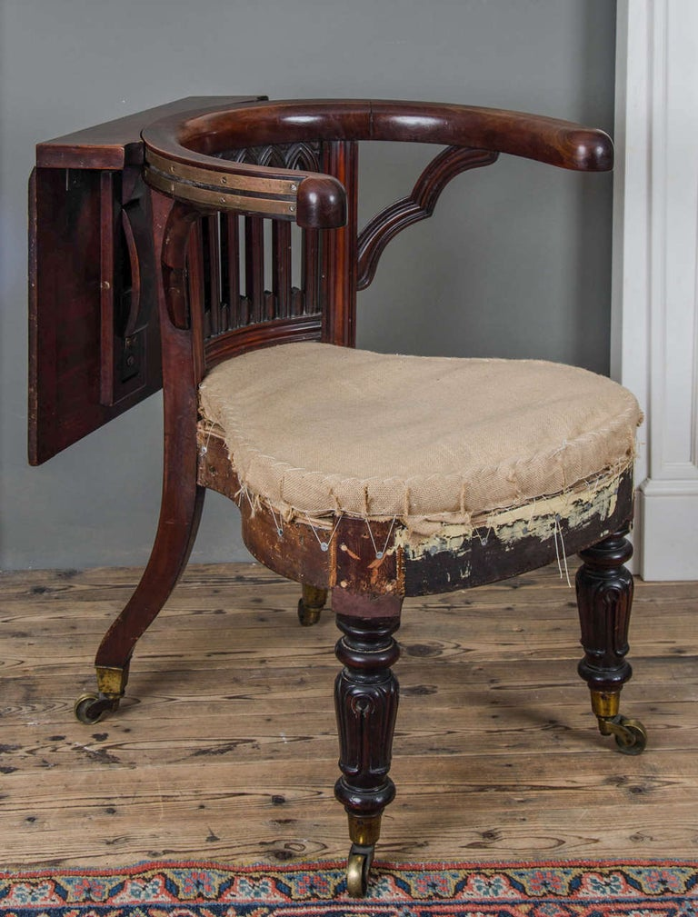 With Gothic arch carved backrest, on turned tapering legs with brass caps and casters, English, circa 1810.