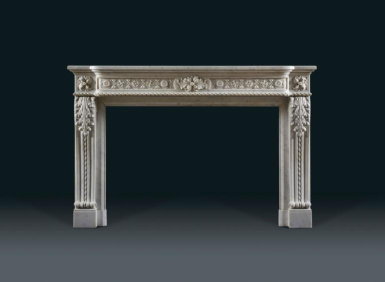 In statuary marble with bowed shaped frieze, centred with an oblong cartouche decorated with budding acanthus and flanked by panels with alternating flower heads in roundels joined by foliate rings. The stepped back jambs of ribbed 'S' shaped