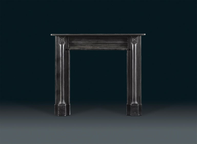 A Regency Belgium black marble chimneypiece is of restrained neoclassical form. The simple, reeded shelf sits above projecting end blocks carved with a stellar motif, and supported on either side by architectural half columns on the jambs. The