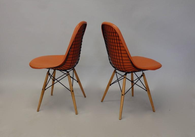 Pair of wood dowel leg Eames dining chairs. Original orange vinyl covers on black wire frames. these look to be of earliest production . Square form cage where base mounts . Several weld repairs .
