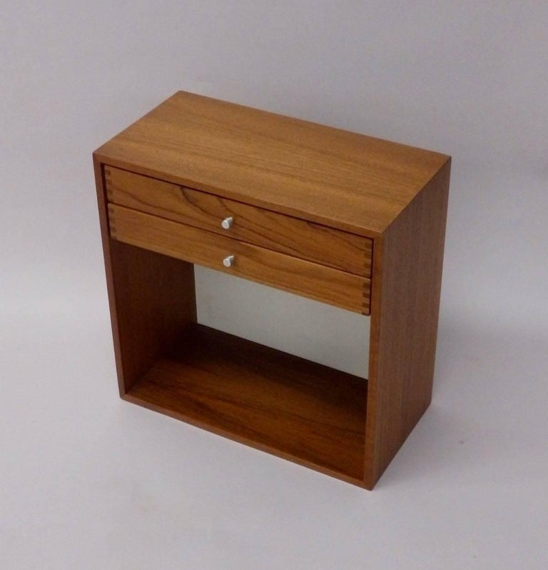 Diminutive teak wall hanging cabinet two drawers with aluminum pulls and dove tail detail over empty shelf space . Ink stamped on back side with makers model number Danish control and designer which is illegible.