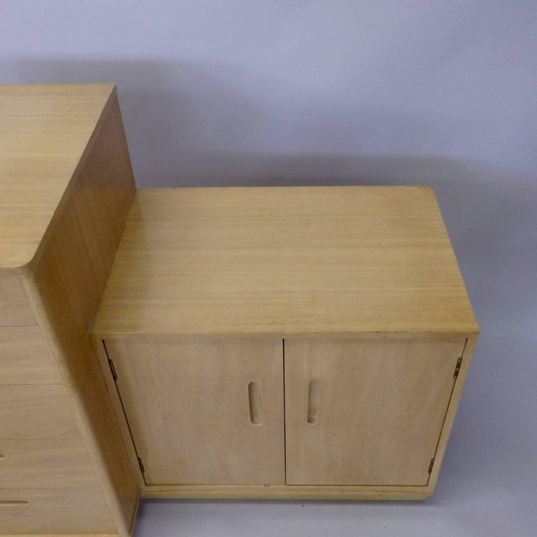Pair of Edward Wormley for Dunbar cabinets. Custom ordered five drawer chest with two-door cabinet on leather wrapped plinth base. Shown in slightly worn but very nice original bleached blonde finish. Dunbar paper tag still intact.