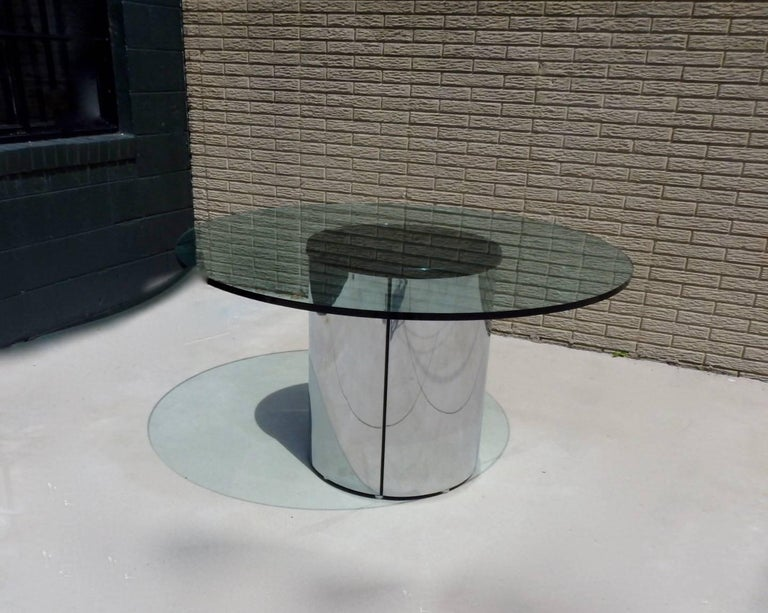 Very clean one inch thick glass top on clean polished stainless steel cylinder base. Attributed to Pace or Brueton.