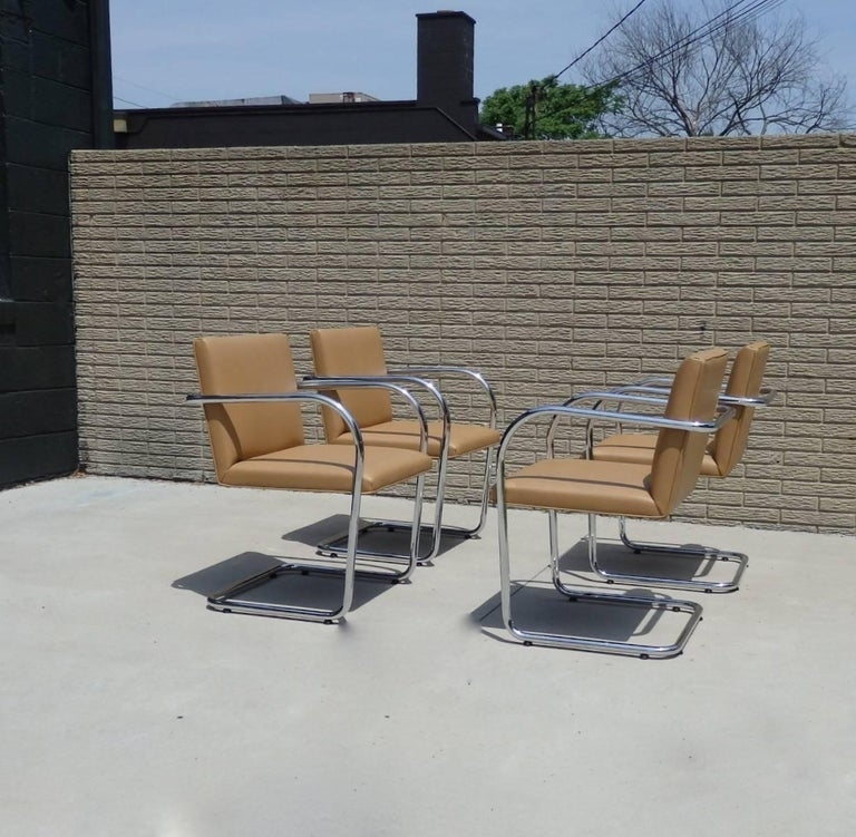 Immaculate set of four Brno chairs. Designed by Mies van der Rohe licensed to Knoll. Signature etched in the arms. Retains paper label underneath. Tubular chrome frames are excellent as is the coffee brown supple Naugahyde.