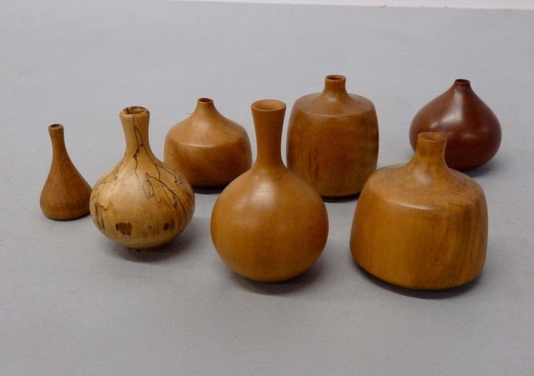 Seven Osolnik turned wood weed pots. Selection of woods and shapes. Smallest being 2.25 tall Largest just under four tall. All signed all excellent. Olivewood, elm, cherry, apple, holly, gum, smallest looks like coconut.
