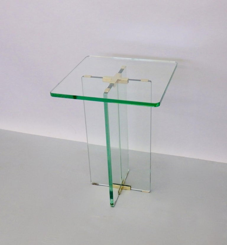 Constructed with four pieces of three quarter inch thick celadon green edge glass. Elements are joined with polished cast brass hardware. This side table is an elegant clean simple architectural design having cross base supporting glass top.