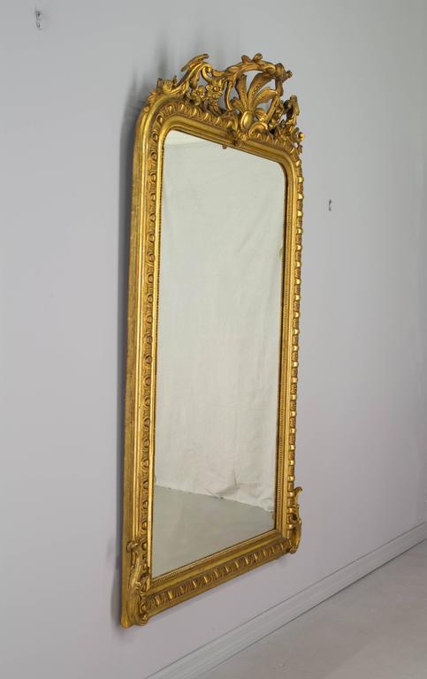 """19th century French Louis-Philippe gilded mirror with carved crest and corner details. Original looking glass. Minor restorations to carvings and touch-ups to gilt. Measures: 67"""" H x 37.5"""" W x 2"""" D (8"""" deep at crest). More photos"""