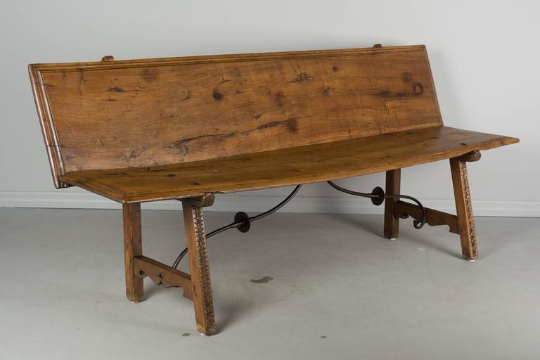 18th century Spanish Baroque style bench made from two solid walnut planks. Beautiful character to the wood with nice grain and natural knots. Waxed finish. Subtle hand-carved detail on the front of the legs. Wrought iron stretcher. Very sturdy with