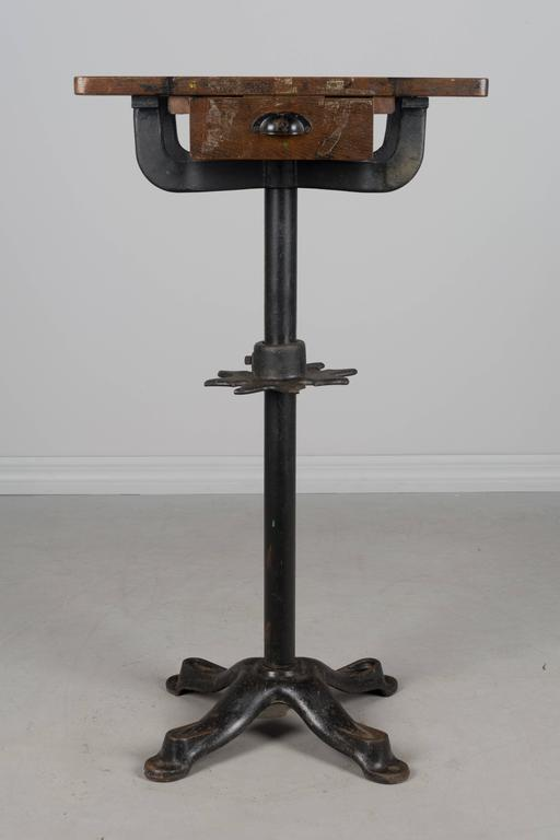 19th century French Industrial work table with cast iron pedestal base. Oak top with one dovetailed drawer. Nice old patina to the wood with black stains and paint residue. A decorative star-shaped cast iron piece on the pole has notches to hold