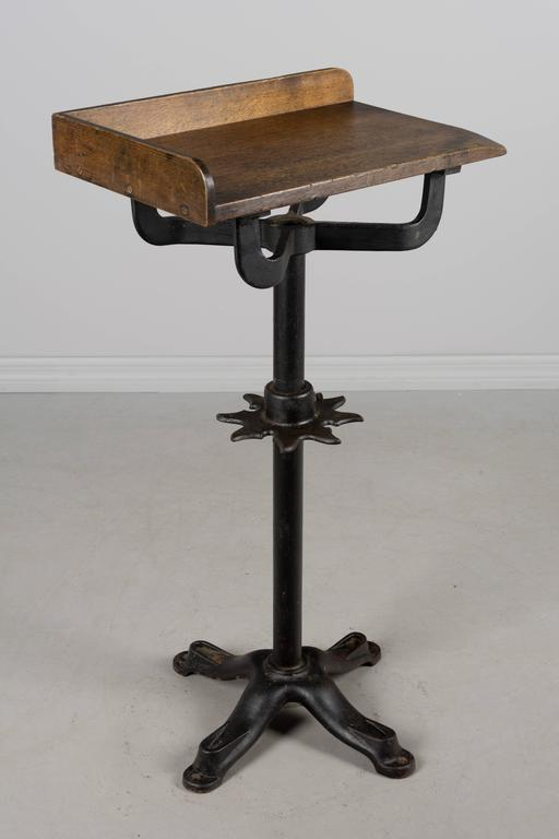 19th century French Industrial work table with cast iron pedestal base. Oak top with worn surface in the corner. Waxed patina. A decorative star-shaped cast iron piece on the pole has notches to hold tools and is adjustable with one bolt holding it