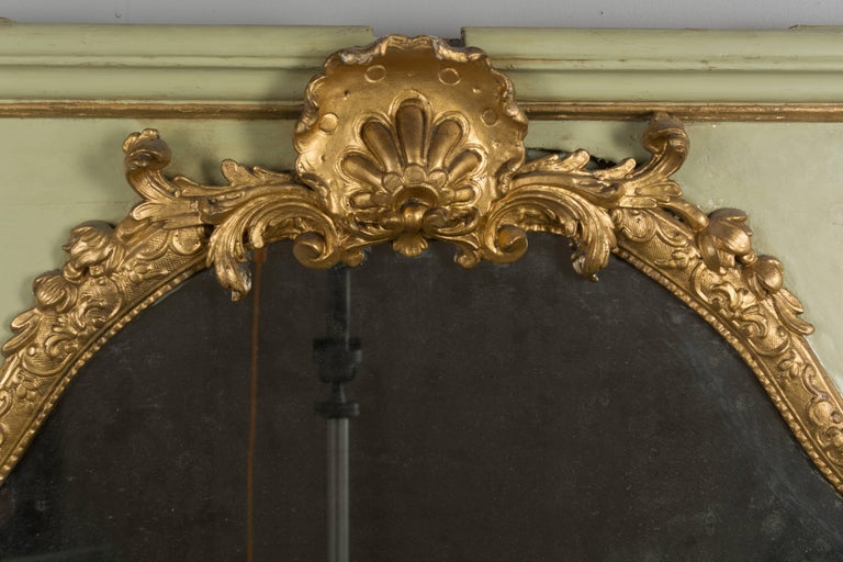 An 18th century Louis XVI French trumeau that was part of a boiseries, or wall paneling. Original mirror in three parts with old silvering. Parcel-gilt frame made of pine with pale green painted surface and gilded carved decoration. Resurfaced paint