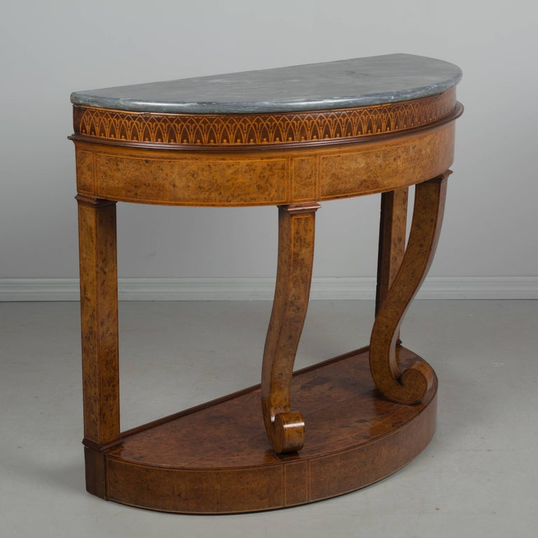 A unique early 19th century Biedermeier demilune console table/jardiniere with original gray veined marble top. Beautiful bird's-eye maple veneer with a decorative band of marquetry inlay. The marble top removes to reveal the original zinc liner for