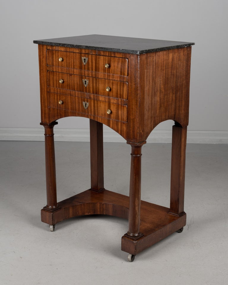 A fine 19th century French Empire marble-top side table made of mahogany veneer with solid oak as a secondary wood. Three dovetailed drawers with original bronze hardware. No key. Original castors. French polish finish. Marble-top was cracked and