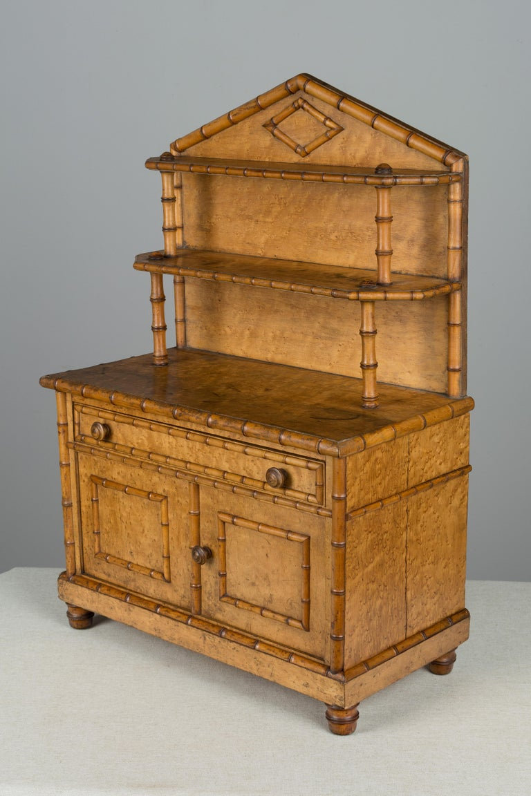 A 19th century French miniature faux bamboo buffet made of bird's eye maple. Well-crafted with tiered shelves on top and cabinet doors opening to a single shelf. A unique large scale doll furniture piece. Left back foot is missing, as found.