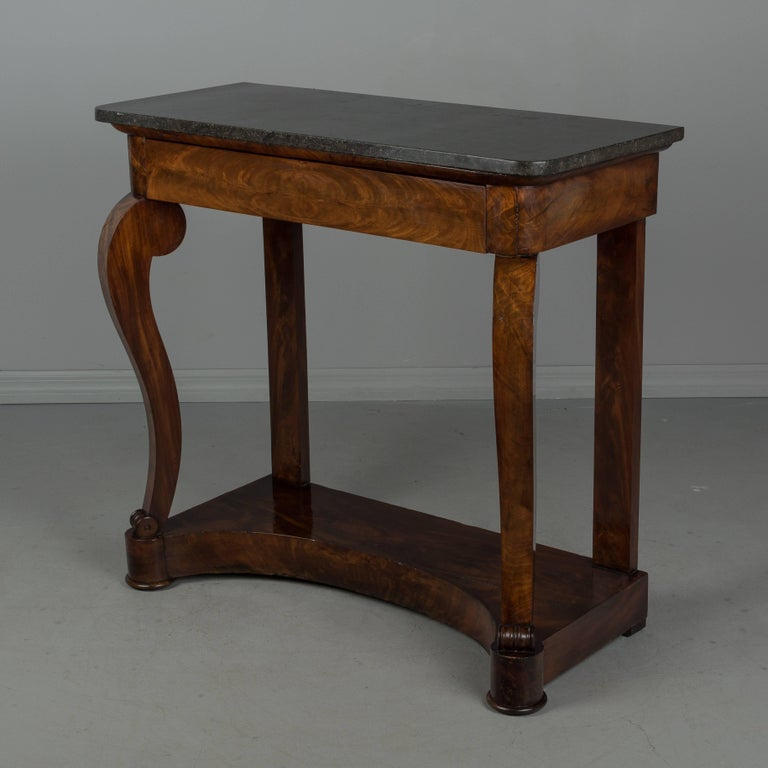 A 19th century French Louis-Philippe period console made of bookmatched veneer of mahogany with oak as a secondary wood. Sculptural front legs ending in scrolls and resting on a plinth base with curved front. Beautiful dark wood grain with French