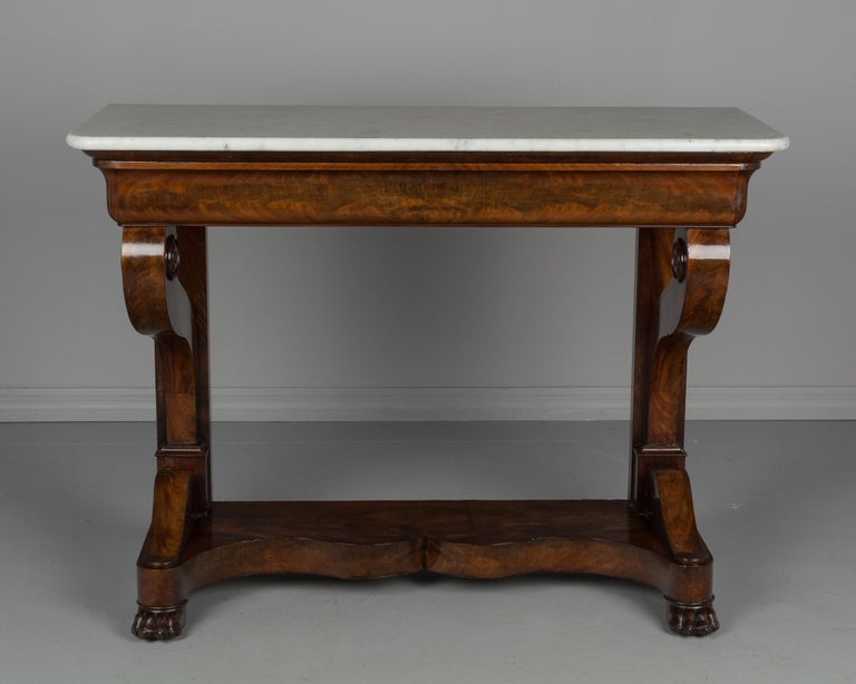 An early 19th century French Louis-Philippe period console made of bookmatched veneer of flame mahogany with oak as a secondary wood. Sculptural front legs ending in scrolls and resting on a plinth base with curved front and lion's paw feet.