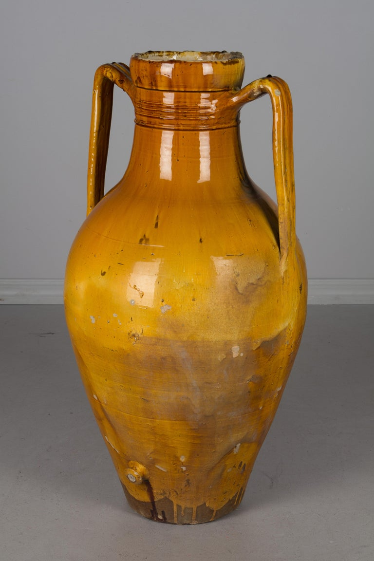 A large 19th century glazed terracotta two-handled pottery urn used for storing olive oil with a small corked spigot at the bottom. Bright yellow ochre glaze. From the Apulia region of Southern Italy. A nice sculptural element for the garden or