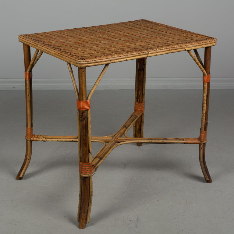 An early 19th century French woven wicker dining set including a small rectangular table, two armchairs and two side chairs. Exceptional craftsmanship and design, having sturdy bamboo frames with x-pattern stretchers and tightly woven tabletop and
