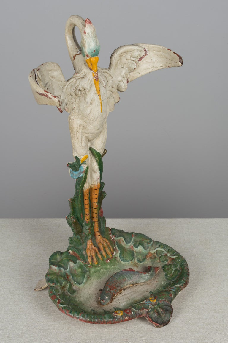 A whimsical 19th century French cast iron polychrome painted umbrella stand. Beautifully detailed sculpture of a crane standing at the water's edge, eyeing a fish in the pond below. The bird's outstretched wings curve to hold the umbrellas upright