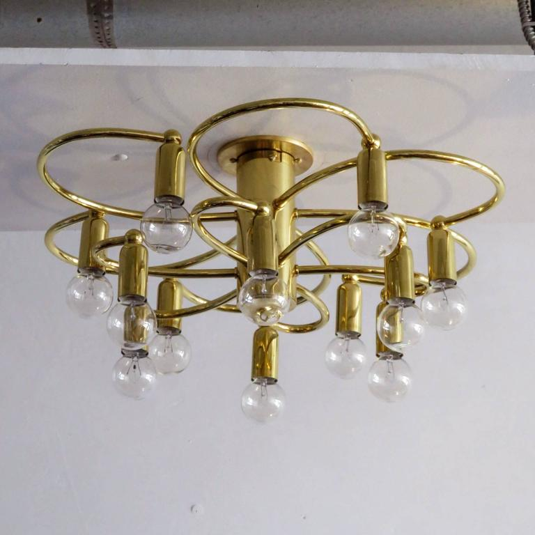 Stunning brass twelve-light flush mount ceiling light by Honsel, Germany with two tiers of six organically shaped arms, with a total of 12 sockets total, can be used as wall sconce as well.