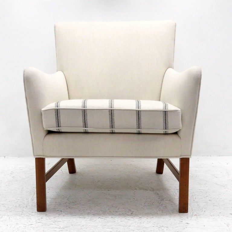 Wonderful lounge chair designed by Ole Wanscher, produced by A.J. Iversen, Denmark in 1960 with egg shell colored wool fabric and lightly striped seat cushion on Cuban mahogany legs, matching settee available.
