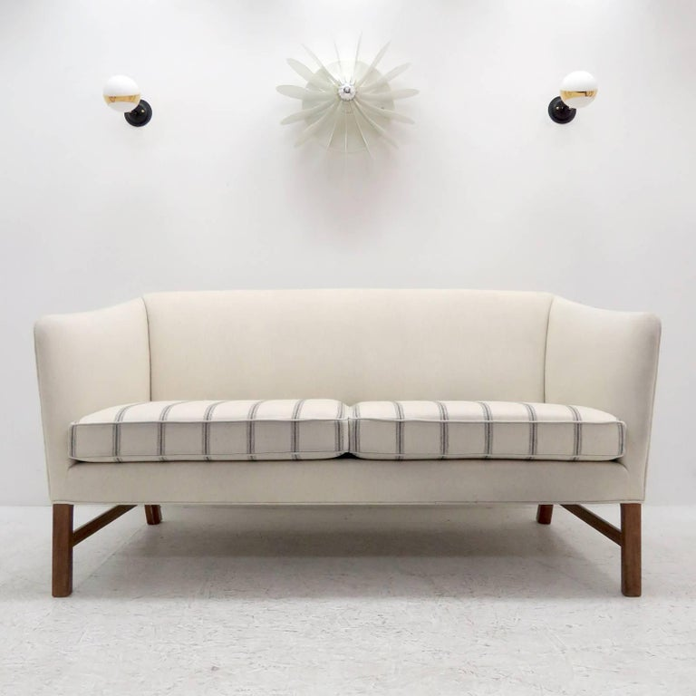 Wonderful settee designed by Ole Wanscher, produced by A.J. Iversen, Denmark in 1960 with eggshell colored wool fabric and lightly striped seat cushion on Cuban mahogany legs.