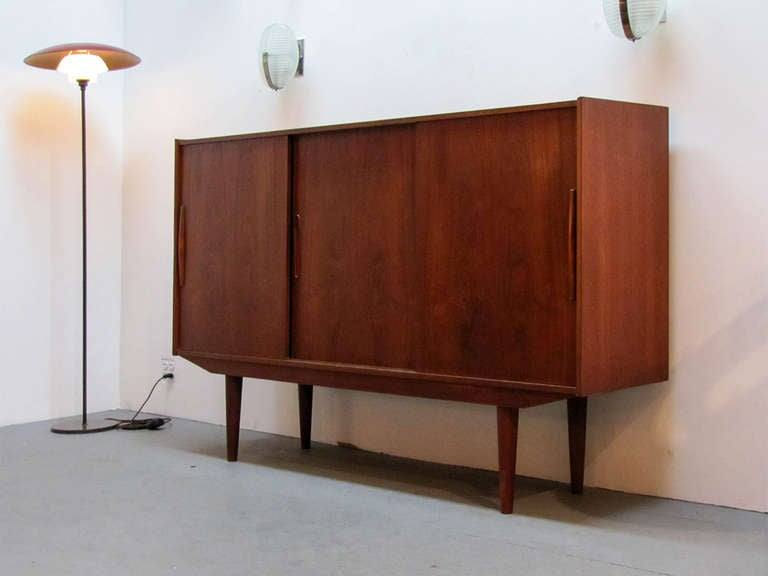 Wonderful tall 1950s Swedish teak credenza by Royal Board, Sweden, with three sliding doors, featuring three shelves in the side compartments and a mirrored shelf setup with three drawers in the center compartment.