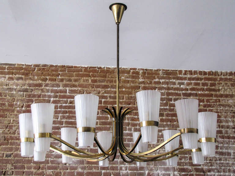 Stunning large decorative German twelve-arm brass chandelier, with two-tone brass arms and textured glass cups.