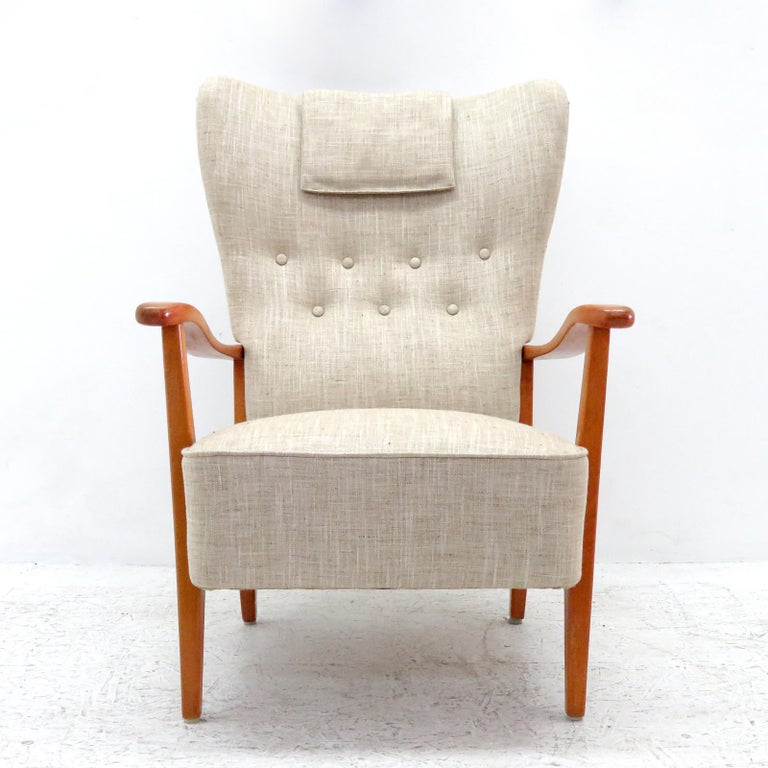 Wonderful Danish modern high back chair by DUX, 1940, sculptural stained beech frame with professionally reupholstered body, the concave wing back is tufted and the seat is spring supported, with detachable head rest cushion, marked. (See also
