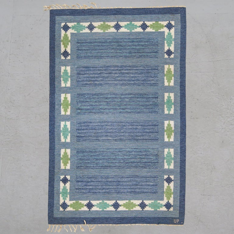Wonderful Swedish flat-weave rug in various shades of blue and green with geometric border compositions. Signed UP.