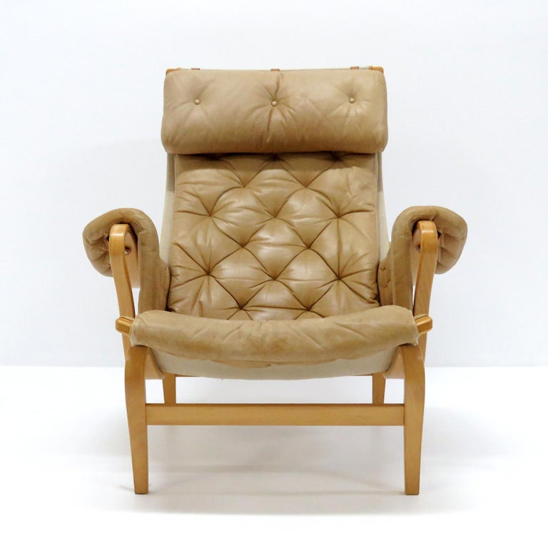 Wonderful early curvilinear lounge chairs by Bruno Mathsson for DUX, composed of a tufted camel color leather cover on canvas, supported by a molded beech plywood frame, with adjustable leather headrest on leather straps, stamped.