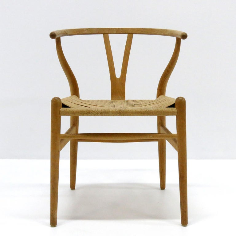 Wonderful set of 7 Model CH-24 dining chairs by Hans Wegner for Carl Hansen & Søn, designed in 1950, in light oak with woven paper cord seat, four seat cushions with significant wear and stains are available on request, marked.