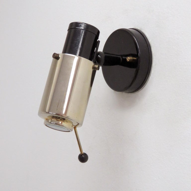 Pair of brass and black enameled wall lights by Jacques Biny for Lita with magnifying lens, handle to adjust angle and direction, provision for on/off pull switch, marked.