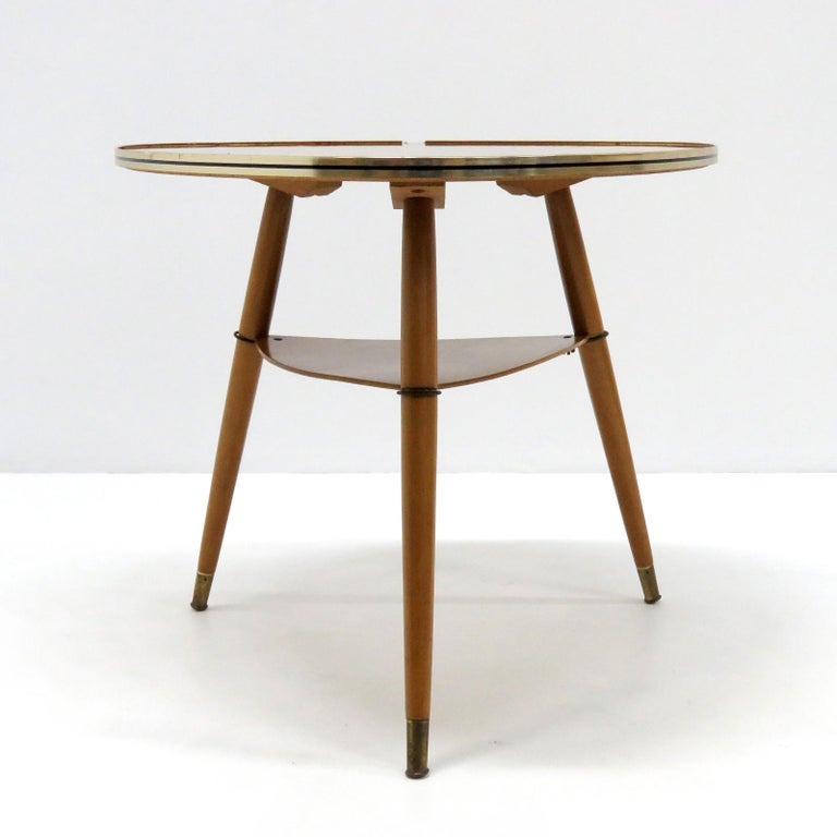 Wonderful 1960s German two-tiered side table in wood and wood veneer with brass band around the triangular tabletop edge, brass hardware and brass feet.