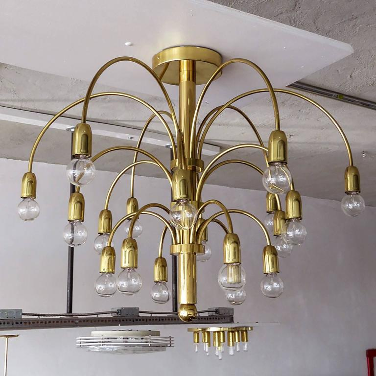 Wonderful German three stage, eighteen-arm fountain chandelier or flush mount in brass with six arms per stage.