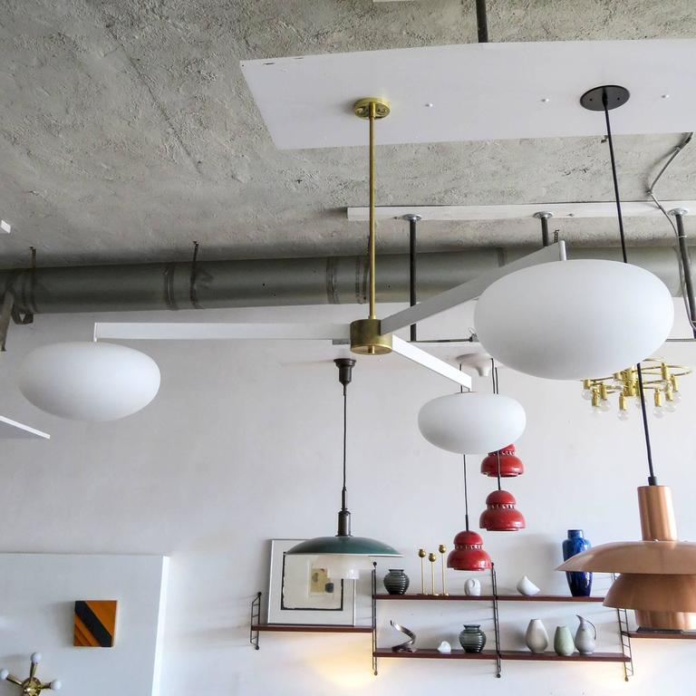 Stunning large-scale three-arm chandelier by Gallery L7, in white enameled steel with brass accents and three matte opaline glass globes, current drop of 32