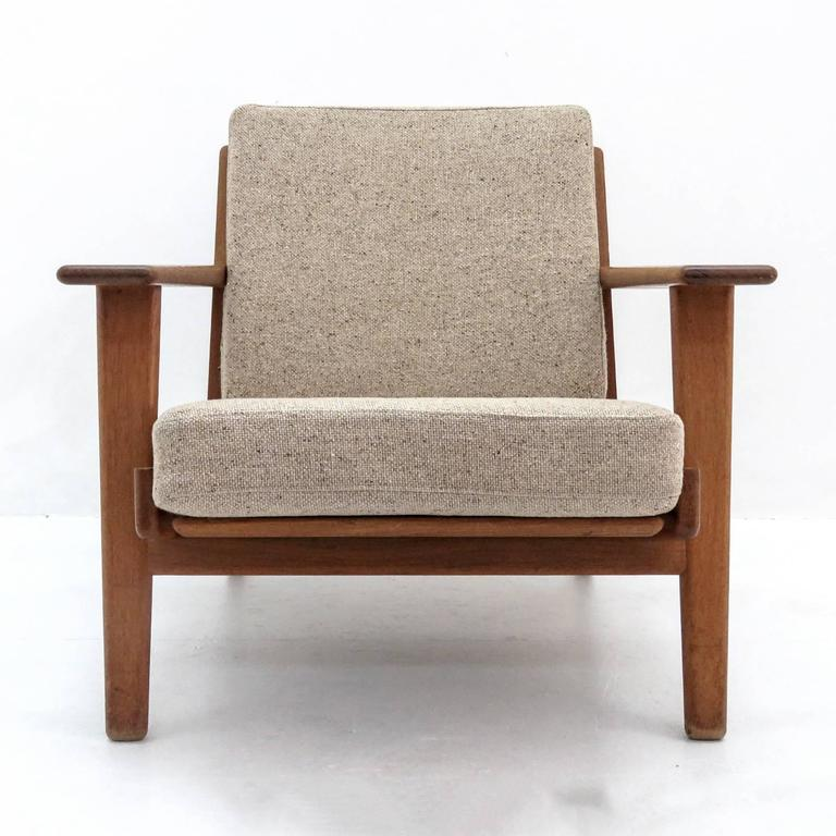 Wonderful lounge chair GE-290, designed by Hans J. Wegner for GETAMA in 1953, solid oak frame with nice patina and upholstered in beige gray wool on original spring cushions, marked.